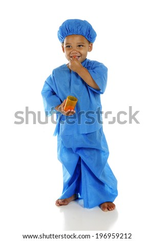 "An adorable preschool ""doctor"" in blue scrubs, happily taking a pill from the pill bottle he holds.  On a white background. - stock photo"