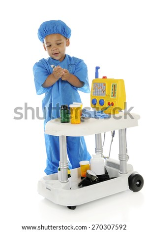 "An adorable preschool ""doctor"" in scrubs, drawing up medicine from a bottle on his emergency cart.  On a white background. - stock photo"