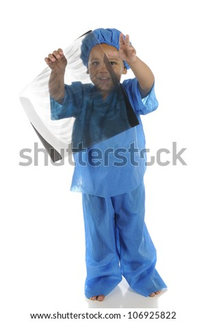 "An adorable preschool ""doctor"" wearing scrubs, happily holding a chest-x-ray and looking through it.  Focus on uncovered eye.  On a white background. - stock photo"