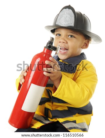 "An adorable preschool ""fire chief"" holding a household fire extinguisher.  On a white background."
