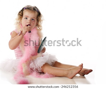 An adorable preschool girl applying makeup while dressed in boas and a petticoat.  Isolated on white. - stock photo
