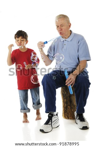 An adorable preschooler and his grandpa blowing bubbles together.  On a white background.