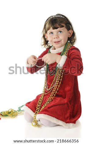 An adorable preschooler dressed up for Christmas happily wearing strands green and gold beads around her neck.  On a white background.