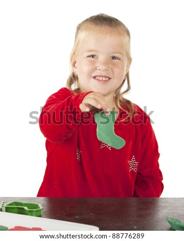 An adorable preschooler happily displaying the Christmas stocking she cut out of green kiddie dough. - stock photo