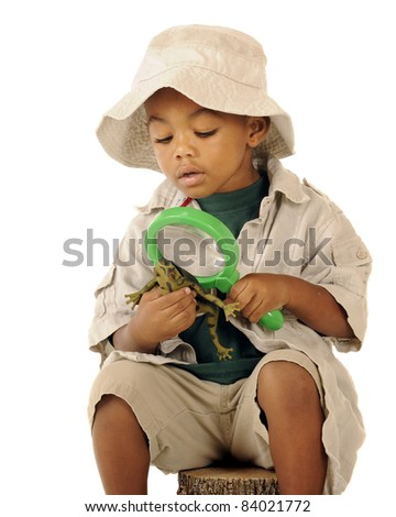 An adorable preschooler in a safari hat and explorer clothes examining a frog's belly with a magnifying glass. - stock photo