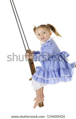 An adorable preschooler in an old fashioned dress and bloomers swinging high on an antique, wooden, self-pumping swing.  On a white background. - stock photo