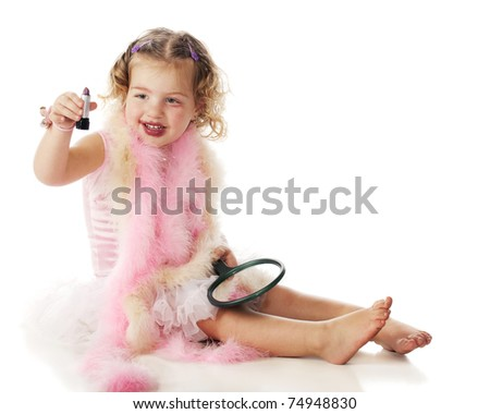 """An adorable preschooler in boas and petticoat holding up the lipstick she's used to make herself """"beautiful."""" - stock photo"""