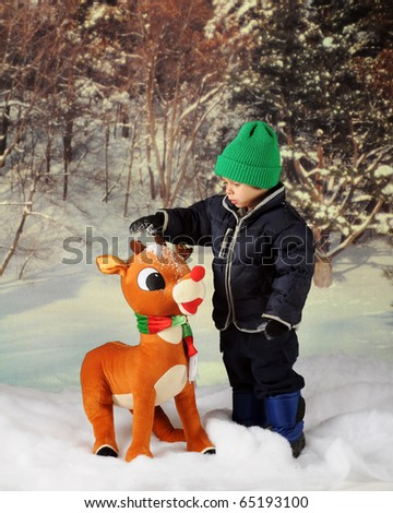 An adorable preschooler in winter wear dumping snow on a large, toy reindeer. - stock photo