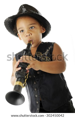 An adorable preschooler playing a toy clarinet in his sparkly fedora and black leather jacket.  On a white background.   - stock photo