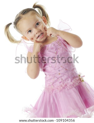 An adorable preschooler poking dents in her cheeks with her fingers while wearing pretty pink princess dress.  On a white background. - stock photo