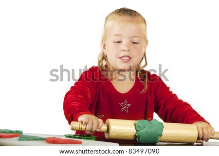 An adorable preschooler rolling out green kiddie dough to make more cookie cutter cutouts for Christmas. - stock photo