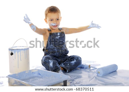 An adorable preschooler sitting among wall-painting supplies.  He's happily clapping his paint-soaked hands.  Isolated on white. - stock photo