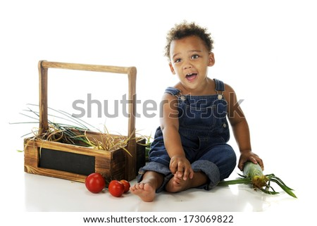 An adorable preschooler sitting barefoot in his overalls with veggies from a wooden basket.  On a white background.
