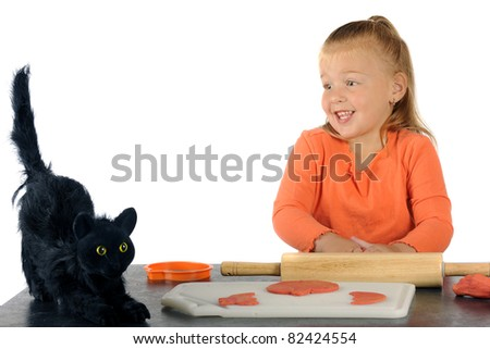 """An adorable preschooler skittish with a furry black cat while making Halloween """"cookies"""" from orange modeling clay. - stock photo"""