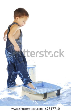 An adorable preschooler stepping in a full paint tin.  Isolated on white. - stock photo