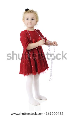An adorable preschooler wearing a sparkly red dress while happily playing with a strand of heart-shaped beads.  On a white background. - stock photo