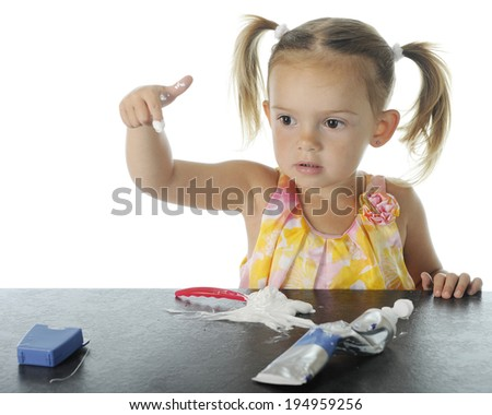 An adorable preschooler who has loaded her own toothbrush with toothpaste.  She's concerned about having it on the tip of her index finger.  On a white background. - stock photo