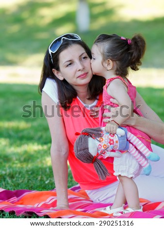 An adorable small child kissing her mother - stock photo