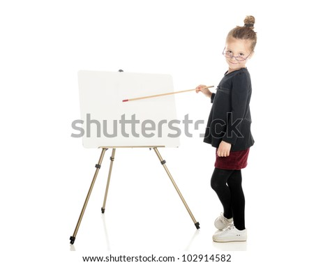 """An adorable """"teacher"""" peering over her glasses while pointing at the white board easel.  On a white background.  (The easel is left blank for your text.) - stock photo"""