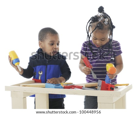 An adorable toddler boy watching what is preschool sister is doing with the toy tools on a workbench.  On a white background. - stock photo