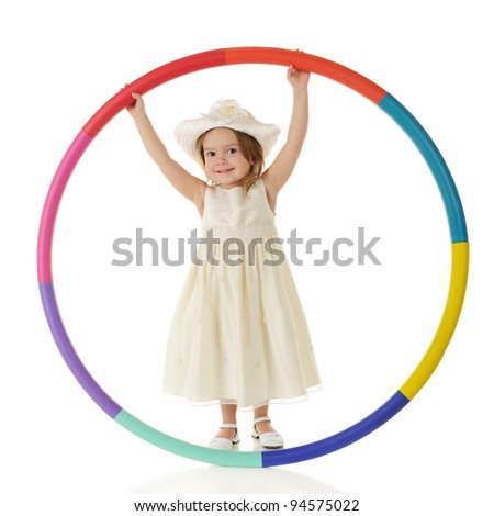 An adorable toddler happily hanging onto the upper edge of a big, colorful hoop.  On a white background. - stock photo