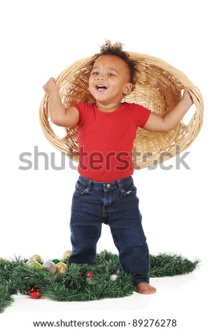 An adorable toddler happily holding a wicker basket from which he dumped Christmas ornaments.  On a white background. - stock photo