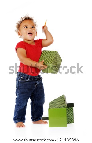 An adorable toddler happily playing with a pencil and gift boxes.  On a white background.