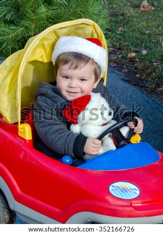 an adorable toddler in a santa hat, drives a little red car with his favorite stuffed polar bear