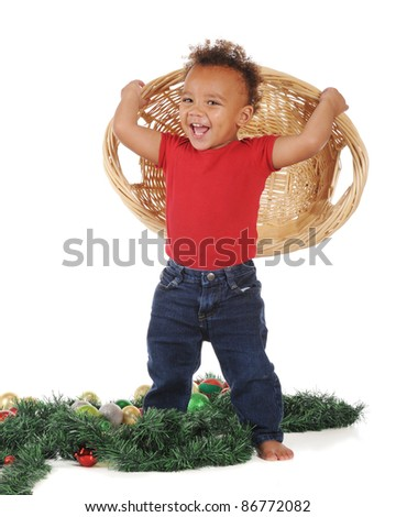 An adorable toddler laughing at the mess he created when he dumped Christmas ornaments from the wicker basket he holds.  On a white background. - stock photo