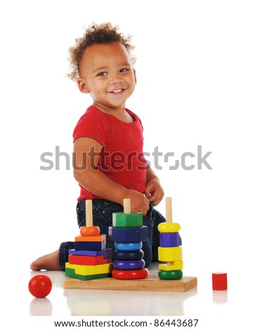 An adorable toddler playing with a stacking toy.  On a white background.