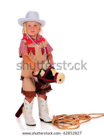 An adorable two-year-old cowgirl ready to ride her stick horse.  Isolated on white.