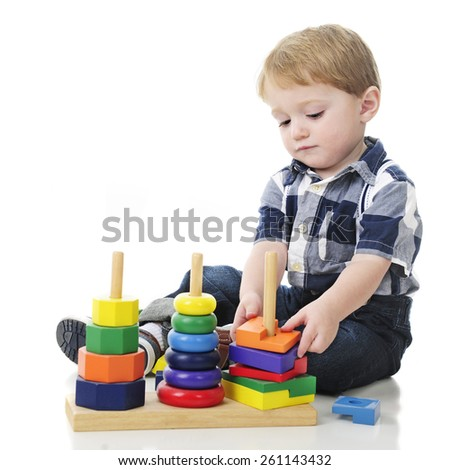 An adorable two year old unstacking a colorful wooden stack toy.  On a white background with plenty of space for your text on the left.   - stock photo