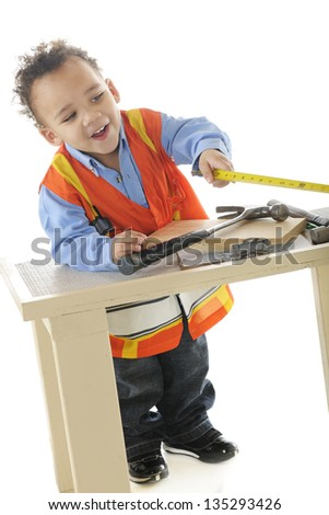 "An adorable 2-year-old ""construction worker"" happily taking measurements.  On a white background."