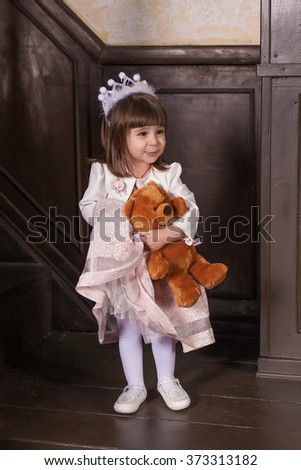 An adorable 2-year-old girl and her toy bear. Little Princess. Portrait in the interior - stock photo