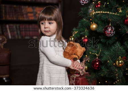 An adorable 2-year-old girl and her toy bear near and her toy bear near Christmas tree. - stock photo