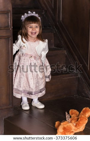 An adorable 2-year-old girl and her toy bear. Portrait Little Princess in full in the interior.  - stock photo