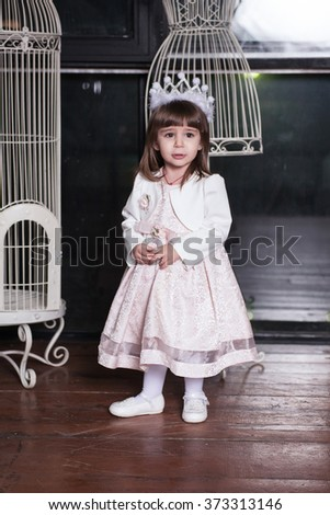 An adorable 2-year-old girl is sad. Little Princess. Portrait in full growth in the interior - stock photo