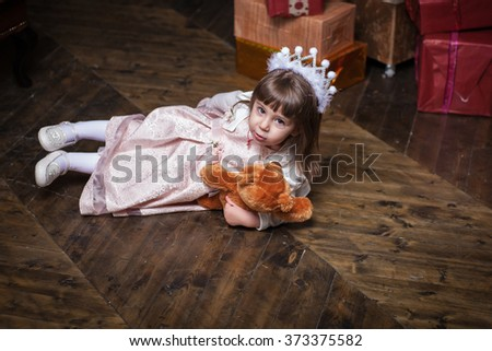 An adorable 2-year-old girl playing on the floor with his toy bear. Next boxes with gifts.  - stock photo