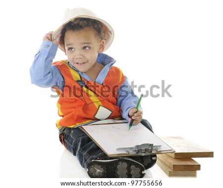 An adorable 2-year-old wiring on a clip board in his construction garb.  On a white background.