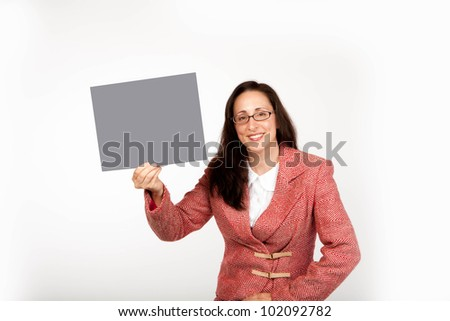 An adult businesswoman wearing a suite on a isolated white background holding up a neutral grey sign with room for copy