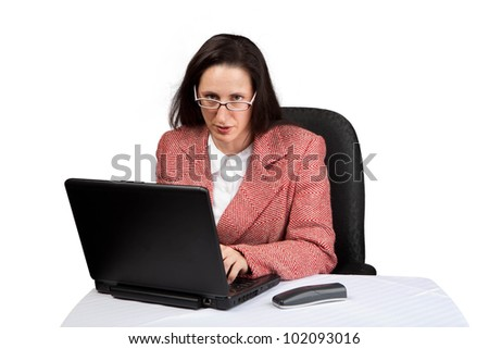 An adult businesswoman wearing a suite on a isolated white background working on a laptop with a phone on her desk