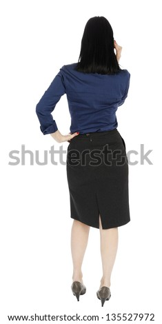 An adult (early 30's) black haired caucasian woman, wearing a blue buttoned blouse and a dark gray skirt; standing with her back to the camera while talking on the phone. Isolated on white background. - stock photo