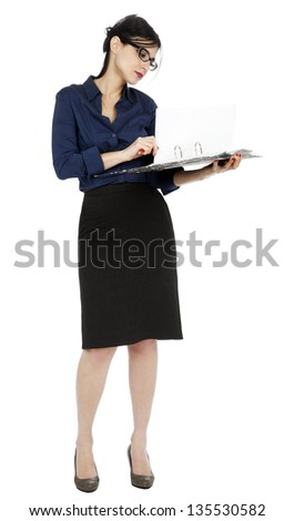 An adult (early 30's) Caucasian woman wearing a blue buttoned shirt and and a dark gray skirt, holding a ring binder folder and flipping a page in the document. Isolated on white background. - stock photo
