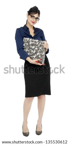 An adult (early 30's) woman wearing a blue buttoned shirt and a dark gray skirt, holding a ring binder folder and a pen while looking at the with a lovely smile. Isolated on white background. - stock photo