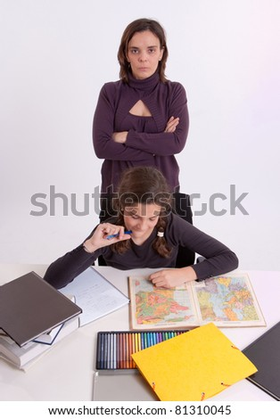 An adult female surveying a young schoolgirl doing her schoolwork - stock photo