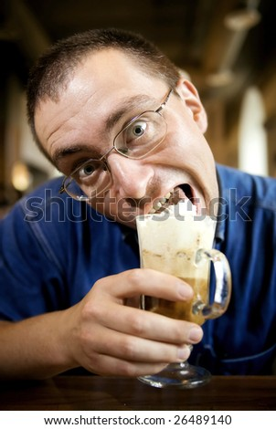 An adult man enjoys his coffee with whipped cream.