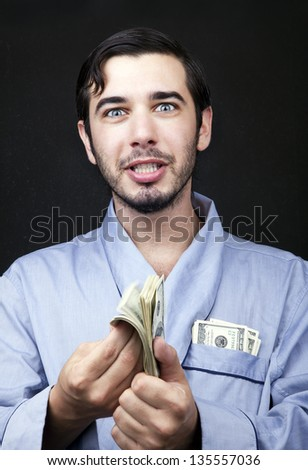 An adult man looking at the camera with an insanely pleased expression, probably because of the stack of 100 US$ bills that he's fluttering in his hands. He is surely working from home. - stock photo