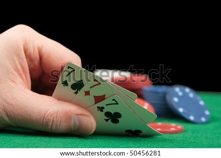 an adult man playing poker . Close-uo of hand. Three sevens