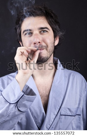 An adult man (30 years old), appears to be quite a bum, looking up with a satisfied look while smoking a marijuana spliff (aka reefer; joint). Dark gray background. - stock photo
