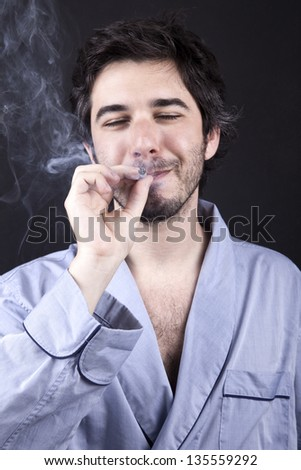 An adult man (30 years old), which  appears to be quite a bum, closing his eyes with a delighted expression while smoking a marijuana spliff (aka reefer; joint). Dark gray background. - stock photo